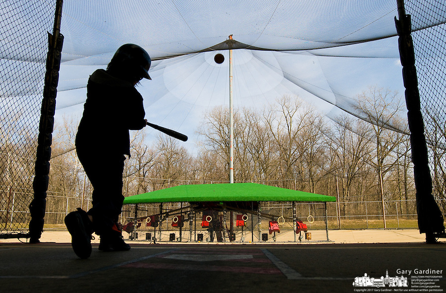 Baseball hopeful hits in a batting cage in early spring in Westerville, Ohio.