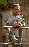A young boy stands on the porch of his home in the Manatuto District of Timor-Leste (East Timor)