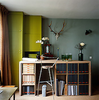 A clever storage unit doubles as a desk to work at and a place for neatly storing box files. A green painted floor to ceiling cupboard fits in the corner