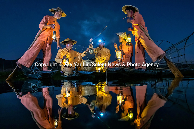 Fishermen are reflected in a lake as they use a traditional technique to catch fish in the shallow waters at sunset.  They use conical baskets, also known as traditional Inle fishing nets, to catch carp and tilapia fish on Inle Lake in Myanmar.<br /> <br /> The Intha fishermen wear unique Inle traditional bamboo hats and are known for rowing their boats with their legs.  SEE OUR COPY FOR DETAILS.<br /> <br /> Please byline: Zay Yar Lin/Solent News<br /> <br /> © Zay Yar Lin/Solent News & Photo Agency<br /> UK +44 (0) 2380 458800