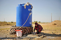 A girl in washes clothes at a water tank in the Swabi Refugee camp. The camp is run by Red Cross/Red Crescent (ICRC), and currently houses around 18,000 refugees. The Pakistani government began an offensive against the Taliban in the Swat Valley in April 2009, which led to a major humanitarian crisis. Up to two million civilians were estimated to have been displaced by the fighting.