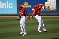 St. Louis Cardinals outfielders Justin Williams (26) and  Austin Dean (0) celebrate closing out a Major League Spring Training game against the Houston Astros on March 20, 2021 at Roger Dean Stadium in Jupiter, Florida.  (Mike Janes/Four Seam Images)