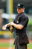 Home plate umpire Junior Valentine gets a new baseball during the Carolina League game between the Frederick Keys and the Winston-Salem Dash at BB&T Ballpark on July 21, 2013 in Winston-Salem, North Carolina.  The Dash defeated the Keys 3-2.  (Brian Westerholt/Four Seam Images)