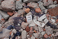 """A clothes tag named """"Max Boy"""" lies in the rubble of a garments factory that collapsed in Savar, near Dhaka, Bangladesh"""