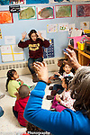 Education Preschool all day program for 3-4 year olds group of children singing song with hand gestures two female teachers singing and demonstrating