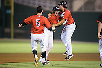Brett Austin (middle) is mobbed by teammates Christian Stringer (right) and John Ziznewski (5) after hitting a walk-off 2-run double in the bottom of the ninth inning against the Asheville Tourists at Intimidators Stadium on June 25, 2015 in Kannapolis, North Carolina.  The Intimidators defeated the Tourists 9-8.  (Brian Westerholt/Four Seam Images via AP Images)
