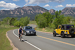 Cyclist and yellow Jeep SUV on mountain road, Boulder, Colorado .  John leads private photo tours in Boulder and throughout Colorado. Year-round.