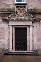 A carved doorway on the south garden front, its weathered pink sandstone facade green with age