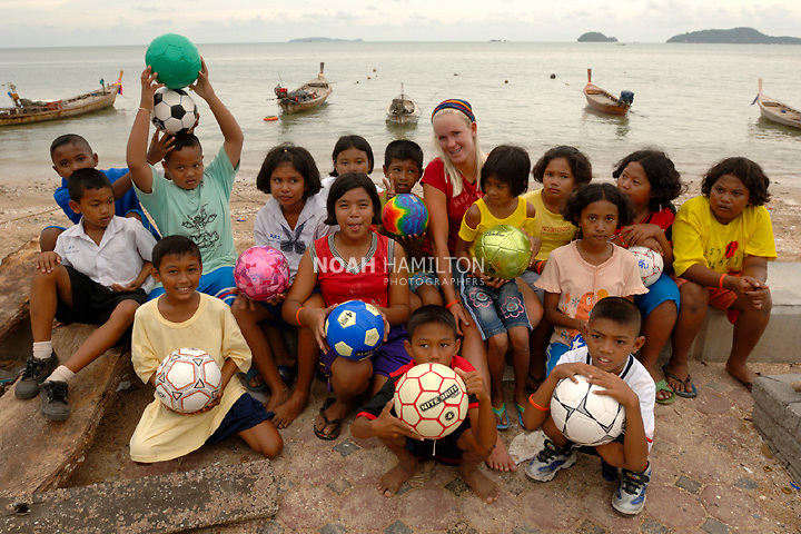A day after giving them surfing lessons on Patong Beach, Phuket, Bethany Hamilton visits the childen from the tsunami devastated sea-gypsy village, Lam Tuk-Kae,and poses for a group picture with them. The community is recovering thanks to help from World Vision and other NGOs. Surfing champion Bethany Hamilton visited the community in August, 2005, to encourage the children. In 2003 Bethany lost her left arm and nearly her life in a shark attack off the north coast of Kauai, Hawaii. But working courageously to adapt to her new physical reality, she returned to surfing competitively and now enjoys her role of public speaking and writing about faith, family and determination.