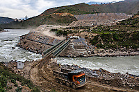 Trucks carry construction material over the Punatsangchu river at the Punatsangchu Hydro Power Project site in Punakha.