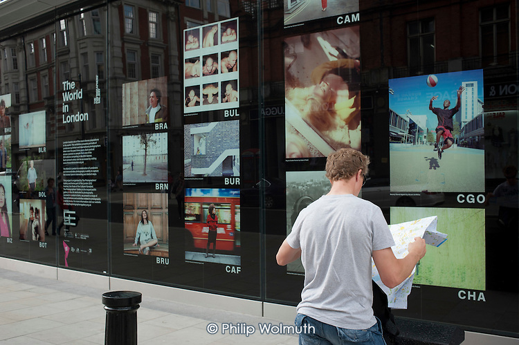 A tourist reads a map by an outdoor photo exhibition organised by the Photographers Gallery in Oxford Street during the London 2012 Olympic Games.
