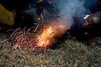A group of boys make a small grass fire for amusement in the Noah's Ark Shelter compound. The shelter  is one of the few places children, known as Night Commuters, can find protection every  night to avoid being abducted by the Lords Resistance Army (LRA) in Northern Uganda. The LRA is primarily made up of abducted youth. Night Commuters find much more than safety in the compounds, they also find friendships, activity and fellowship. Tens of thousands of children, on average, make this exodus every evening. The war in Northern Uganda has been transpiring for two decades. Gulu, Gulu District, Uganda, Africa. December 2005 © Stephen Blake Farrington