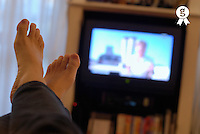 Man watching television, feet up, focus on foreground (personal perspective) (Licence this image exclusively with Getty: http://www.gettyimages.com/detail/73532514 )