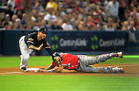 Jun. 4, 2011; Phoenix, AZ, USA; Washington Nationals base runner Ian Desmond is hit in the groin by the ball as he slides safely into third ahead of the tag by Arizona Diamondbacks third baseman Ryan Roberts in the first inning at Chase Field. Mandatory Credit: Mark J. Rebilas-