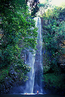 Couple splashing in pool at the base of Secret Falls, Wailua River State Park, Kauai