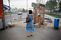 """CHINA. Beijing. A woman looks through a fence, trying to catch a glimpse of the new Olympic park. In recent years construction has boomed in Beijing as a result of the country's widespread economic growth and the awarding of the 2008 Summer Olympics to the city. For Beijing's residents however, it seems as their city is continually under construction with old neighborhoods regularly being razed and new apartments, office blocks and sports venues appearing in their place. A new Beijing has been promised to the people to act as a showcase to the world for the 'new' China. Beijing's residents have been waiting for this promised change for years and are still waiting, asking the question """"Where's the new Beijing?!"""". 2008"""