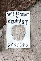 """A sign reading """"This is what a feminist looks like"""" hangs on a statue as people gather in the National Mall area of Washington, DC, for the Women's March on Washington protest and demonstration in opposition to newly inaugurated President Donald Trump on Jan. 21, 2017."""