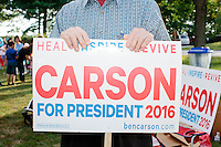 A man holds a Carson sign as Republican presidential candidate Dr. Ben Carson meets with people at Londonderry Old Home Day in Londonderry, New Hampshire.
