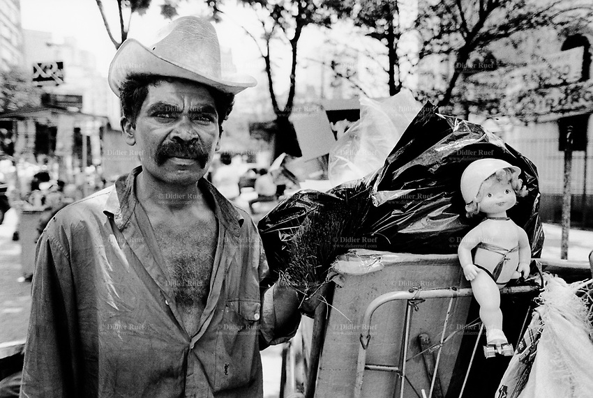 """Brazil. Sao Paulo state. Sao Paulo. Jose is 38 years old. He is a poor man who lives in the street. He stands close to his cart which belongs to """"El Gringo"""", owner of a buy-off center for recycled products. The """"catadores"""" are men who collect paper, plastics, metals, bottles ... in order to sell these items as recycled materials and make a living. Waste collector. © 1994 Didier Ruef .."""