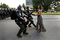 Lone activist Ieshia Evans stands her ground while offering her hands for arrest as she is charged by riot police during a protest against police brutality outside the Baton Rouge Police Department in Louisiana, U.S.A. on July 9, 2016. Evans, a 27-year-old Pennsylvania nurse and mother to a young boy, traveled to Baton Rouge to protest the shooting of Alton Sterling, a 37-year-black man and father of five, who was shot at close range while being held down by two white police officers. The shooting, captured on cell phone videos, aggravated the unrest that has coursed through the United States for two years over the use of excessive force by police, especially against black men.