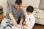 Father with an interest in World War II airplanes and battleships playing with his 6 year old son, who shares his passion, looking at book on battle