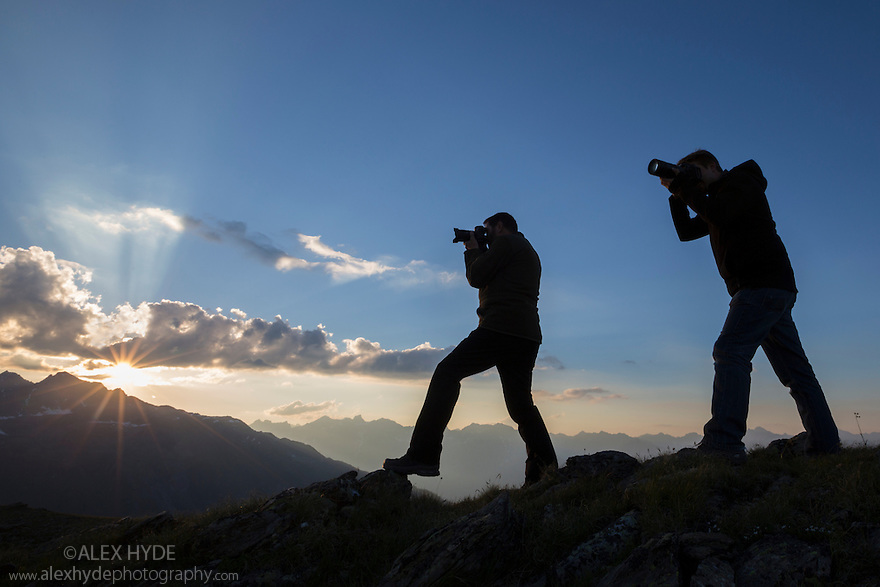 Photographers at sunset recording the mountain landscape of the Samnaungruppe, a subgroup of the Central Alps. Nordtirol, Austrian Alps. July.