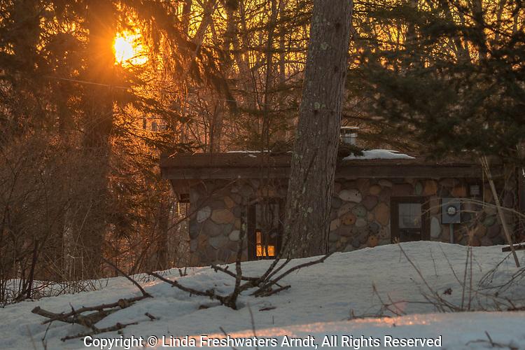 The rising sun illuminates a stone cabin in northern Wisconsin.