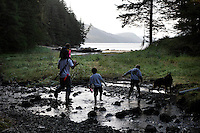 A family walks back to a fish camp on private land that has been in John Littlefield's family since Alaska was given to Tlingit and other native people.  They invite children and elders for a weekend outing who arrive by boat and carry belongings to Dog Point Fish Camp on an island near Sitka in Southeast Alaska.