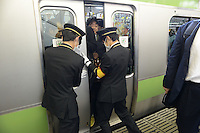 Railway staff squeeze passengers onto full trains and force the doors closed during morning rush hour, Shinjuku Station, Tokyo. With up to 4 million passengers passing through it every day, Shinjuku station, Tokyo, Japan, is the busiest train station in the world. The station was used by an average of 3.64 million people per day.  That's 1.3 billion a year.  Or a fifth of humanity. Shinjuku has 36 platforms, and connects 12 different subway and railway lines.  Morning rush hour is pandemonium with all trains 200% full. <br /> <br /> Photo by Richard jones / sinopix