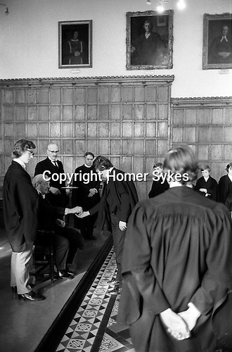 Kings Scholars line up and collect their annual traditional 3d piece from the College Provost. Known as Threepenny Day. Eton near Windsor Berkshire, England 1975.<br /> <br /> Kings Scholars or Collegers as they are known line up to receive a new threepenny piece from the Provost in a 400 years old tradition.<br /> <br /> Dr Roger Lupton 1456–27 February 1539 or 1540 was an English ecclesiastic, lawyer-cleric, chaplain to Henry VII and also to Henry VIII and Provost of Eton from 1502-1535.( The chairman of Eton's governing body. )   His death is commemorated each year on 27 February at Eton College. <br /> <br /> The annual distribution took place after lunch in the College Hall by the Provost Harold Caccia,(Provost 1965-1977) and was confined to the seventy Kings Scholars. Originally the Provost received 2s 8d, other members of staff 1s 4d and less depending on status. Scholars and choristers received 1d each. The scholars still received the one penny in a three penny pieces, the other twopence being from the gift of Provost Bost who succeeded Lupton.<br /> <br /> With the introduction of decimal coinage in 1972, and the abolition of the threepenny piece. Provost Caccia bought up large stocks of redundant coin to ensure continuation of this custom.<br /> <br /> The Captain of School, Provost Harold Caccia, The College Butler with tray and  Master-in-College, Rev. Canon P. Pilkington.<br /> <br /> The Captain of the School would get any 3ds left over owing to absentees.