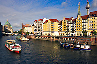 Germany, Berlin.  Nikolai-viertel.  Water front onto the River Spree with tourist boats and Dom, Cathedral, in the distance.
