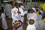 """The Celestial Church of Christ London. Pastors shows children members of the congregation toys which have been brought for them.  from A STORM IS PASSING OVER a Look at Black Churches in Britain. Published by Thames and Hudson isbn 0 500 27826 1 This west African church was founded by S B J Oshoffa Mainly attended by Yoruba people from western Nigeria the church  flourishes with offshoots in London Paris and New York This  photograph is taken from the book The Storm is Passing Over"""""""