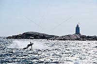 A thrill seeker kiteboards past the Sakonnet Point Light.