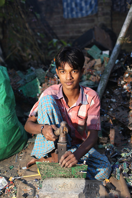 In the village of Sangrampur, a yboy dismantles electronic waste, collected for recycling and reselling in nearby Kolkata, India. November, 2013