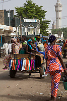 Senegal, Touba.  Street Scene.  Women Riding Horse-drawn Cart after Shopping.