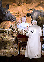Pope Benedict XVI arrives to pray in front of the nativity in Saint Peter's Square after celebrating the Vespers and Te Deum prayers in Saint Peter's Basilica at the Vatican on December 31, 2009