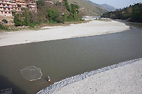 A fisher man catches fish in the Indravati River, Outside of Kathmandu, Nepal. May 1, 2015