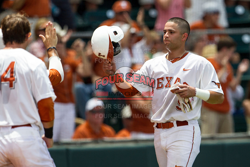 Texas Longhorns shortstop CJ Hinojosa (9) is greeted at the dugout after scoring during the NCAA Super Regional baseball game against the Houston Cougars on June 7, 2014 at UFCU Disch–Falk Field in Austin, Texas. The Longhorns are headed to the College World Series after they defeated the Cougars 4-0 in Game 2 of the NCAA Super Regional. (Andrew Woolley/Four Seam Images)
