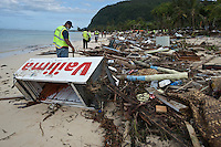 Police officers and volunteers search amongst debris strewn across the beach at Lalomanu. More than 170 people died when a tsunami triggered by an 8.3 magnitude earthquake hit Samoa and neighbouring Pacific islands on 29/09/2009. Samoa (formerly known as Western Samoa)..