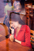 Young woman in a coffee house talking on a cell phone