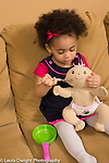 21 month old toddler girl sitting on couch pretend play feeding doll with spoon