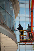 Workers on a hoist clean the windows on City Hall, London.