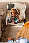 17 month old toddler boy looking at self in mirror recognizing self wearing lion winter hat