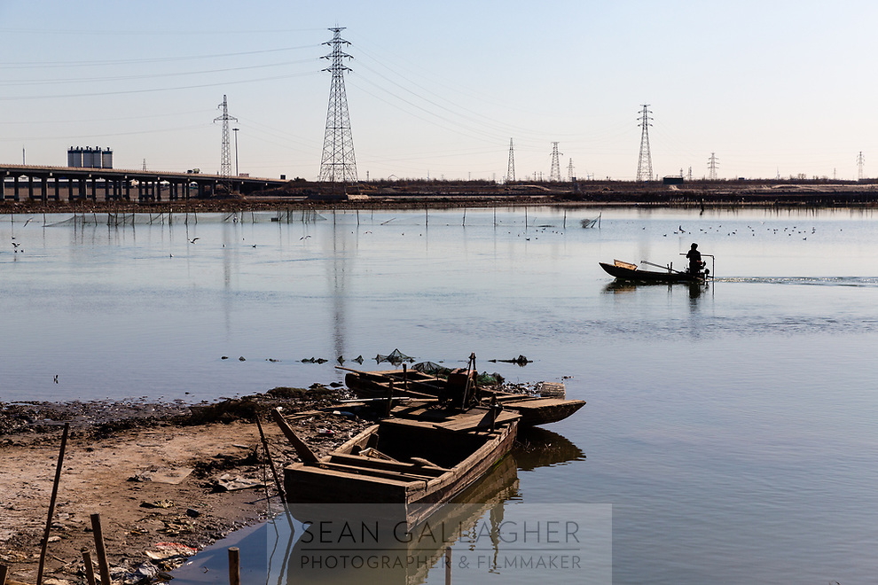 A fisherman journeys along a river at low tide in downtown Tianjin. Coastal erosion is already a severe problem for much of the low lying land in the region and is predicted to get worse as climate change impacts continue to intensify. 2019