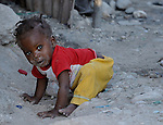 A child crawls in the dirt in Cite Soleil, a poor neighborhood of Port au Prince, Haiti, where cholera is epidemic almost one year after a devastating earthquake leveled the capital.