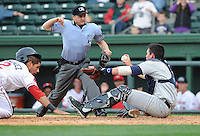 Catcher Jayson Hernandez (12) of the Greenville Drive slams into catcher Peter O'Brien (9) of the Charleston RiverDogs while trying to score what would have been the winning run on a hit in the bottom of the seventh inning of a game on Saturday, April 6, 2013, at Fluor Field at the West End in Greenville, South Carolina. Charleston went on to win Game 1 of a doubleheader, 6-2. (Tom Priddy/Four Seam Images)