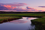 Elk antler creek meanders through Hayden Valley, the clouds and sky colored by the sunset.<br /> Yellowstone National Park, Wyoming