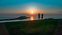WEATHER PICTURE WALES<br /> A young couple take a picture as the sun sets over Worms Head at the end of a warm sunny day in Rhossili, Gower Peninsula, Wales, UK.