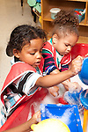 Education preschool first days of school 2-3 year old water table boy and girl in smocks playing separately
