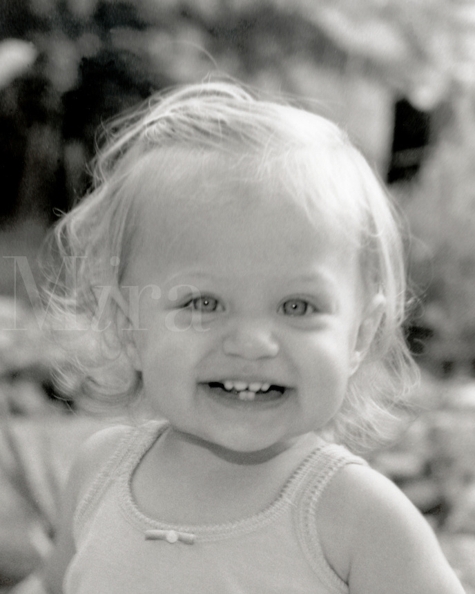 Black and white image of a one year old blonde girl with blue eyes with an excited smile.
